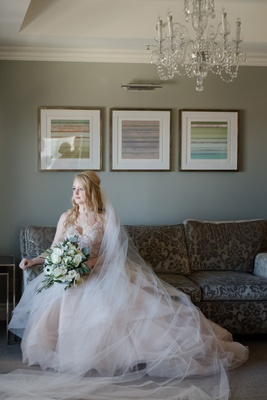 bride in martina liana layered blush ballgown sitting on sofa carrying bouquet of ivory and greenery