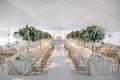 white tented wedding reception space tall tree centerpieces long king's tables round tables around