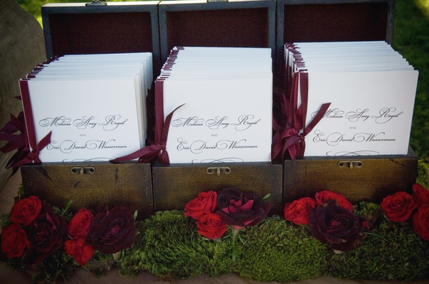 Wood box holding burgundy and white booklets
