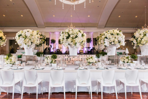 White head table at ballroom wedding with white chairs, white tablecloth, white centerpieces