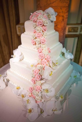 White wedding cake with square layers decorated with pink and white sugar roses and fresh orchids