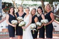 Bride in a sleeveless Claire Pettibone dress, bridesmaids in short, lace, blue Tadashi Shoji dresses