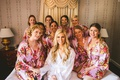 wedding getting ready photo bride in white robe bridesmaids in pink flower print robes on bed