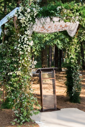 Outdoor Jewish wedding ceremony greenery chuppah with shawl on top mother of bride