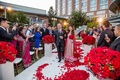 Indian bride walking with dad down red petal aisle