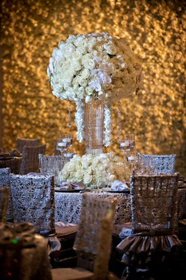 Tall flower arrangement centerpiece with white orchid and ivory rose flowers in front of flower wall