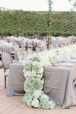 Grey reception table with white and green hydrangeas