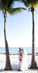 Bride and groom kiss under palm trees in Key West