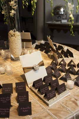 Place card table covered with a golden tablecloth and topped with chocolate brown place cards