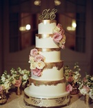 Tall white wedding cake with gold brush strokes on top and fresh pink white roses gold monogram