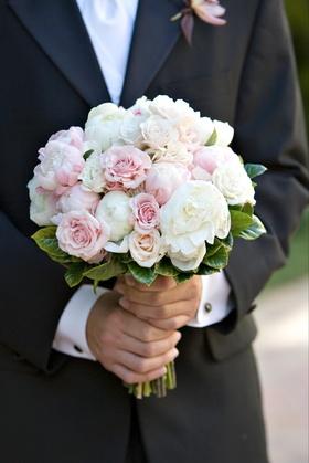 Groom holding bridal flowers