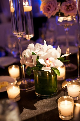 Candle votives surrounding white orchid arrangement