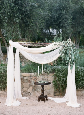 Rustic wedding ceremony structure with white fabric and green leaves for outdoor wedding ceremony
