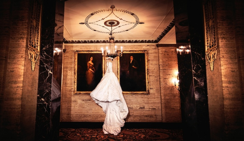 Wedding dress hanging from chandelier next to paintings