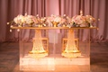 glass sweetheart table with gold trim and crystal chandeliers in the base