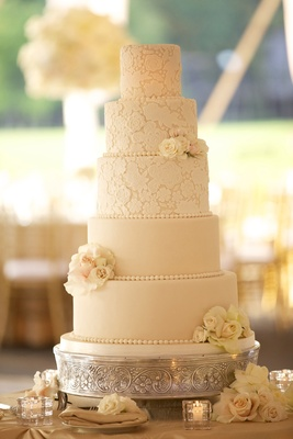 Ivory wedding cake with lace pattern and fresh flowers