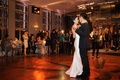Strapless wedding dress dancing with groom in tuxedo bride smiling guests watching and taking photo