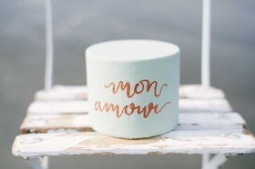 small light blue cake with rose gold calligraphy saying mon amour on a wooden chair