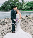 bride and groom on island of maui in hawaii destination wedding couple portrait purple flowers