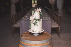 White wedding cake with fresh flowers, leaves and branches