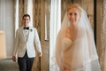 Groom in white tuxedo jacket bow tie glasses walking toward bride in veil and strapless gown wedding