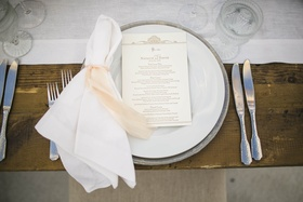 Wooden table topped with white napkin and pink tie