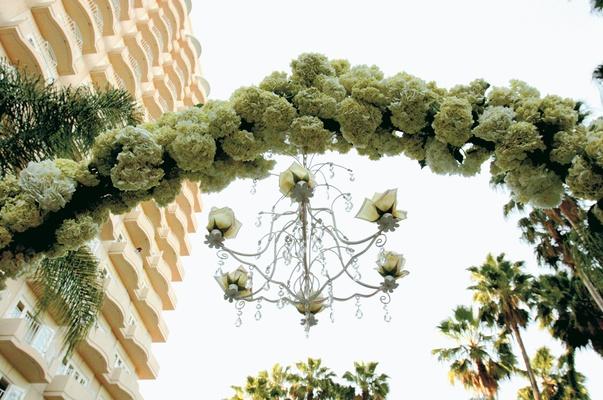 White hydrangea and gardenia flowers on iron gate with chandelier