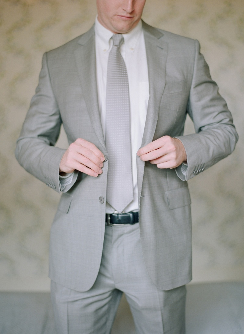 Groom buttoning grey suit jacket and silver tie