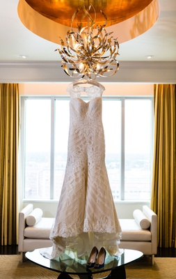 Wedding dress with keyhole back hanging from odern chandelier artwork in hotel room skyline wedding