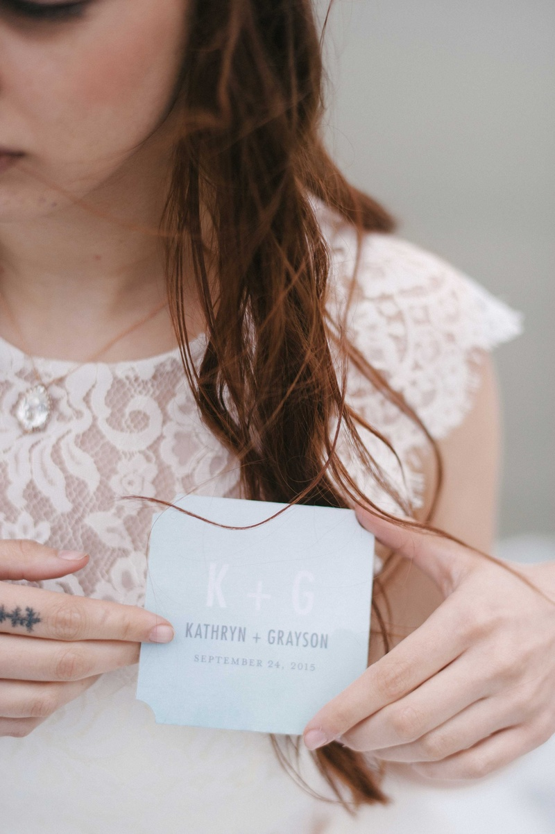 bride held a blue paper product with the bride and grooms initials names and the wedding date