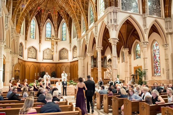 bridesmaid and groomsman processional church wedding chicago tall arches stained glass greenery