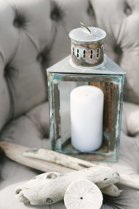 a chipped blue and gray lantern with a white candle pieces of driftwood sand dollar on gray chair
