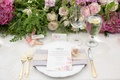 Bridal shower guest place setting with flower print menu card, gold flatware, and cookie favor