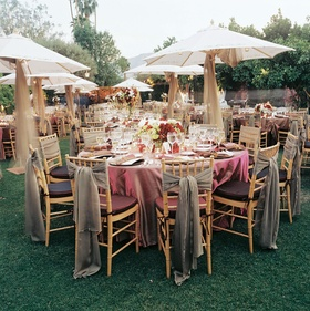 Drapery hangs from white umbrellas and tied to reception chairs