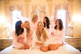 Bride in white robe lace trim bridesmaids in light pink robes on bed in bridal suite