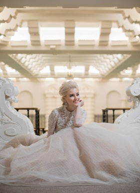 Bride sitting down in long sleeve ball gown point d'esprit skirt embellished bodice long sleeves