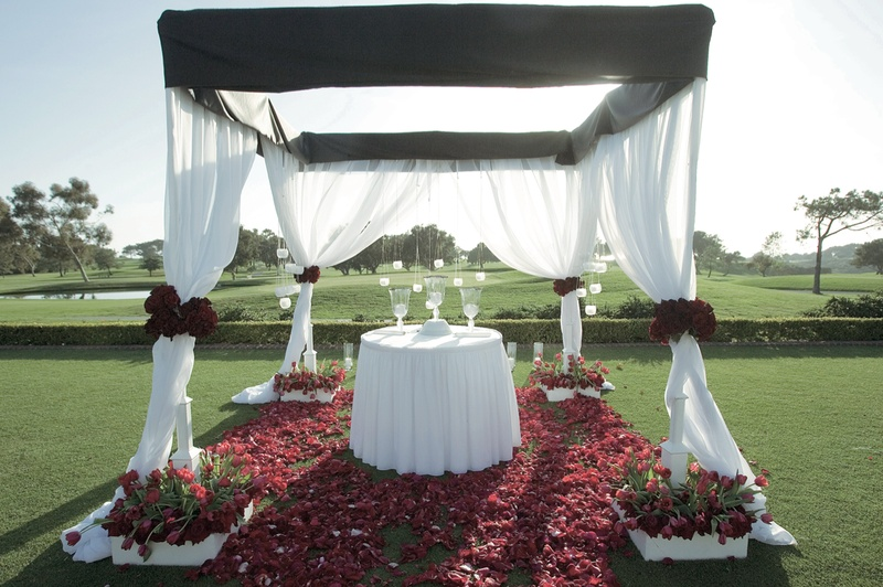 Black and white ceremony structure with red rose petals on golf course