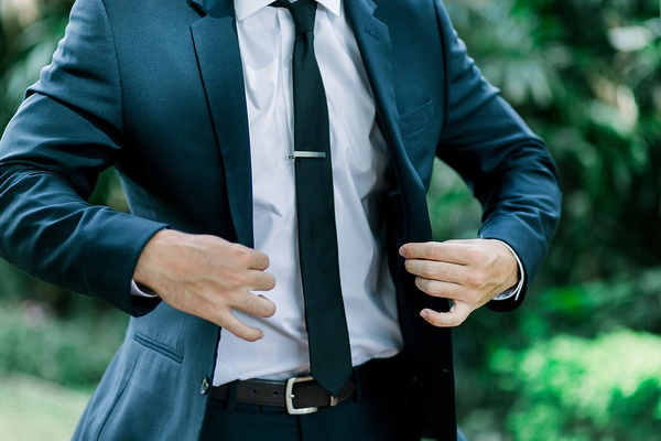 groom in dark suit putting on jacket skinny tie tie clip outdoor wedding