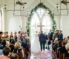 wedding ceremony bride and groom altar cross arch window greenery flower petals wood floor pews
