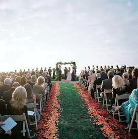 Oceanfront wedding ceremony on grass lawn with flower petals