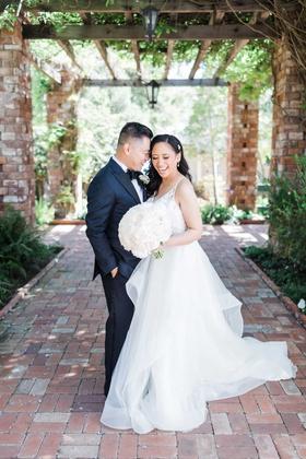 wedding portrait brick flooring and wood beams greenery black tuxedo and hayley paige wedding dress