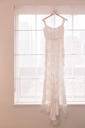 Lace bridal gown with sheath silhouette on custom hanger
