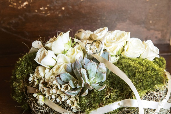 two wedding rings on bed of moss, white roses, succulents