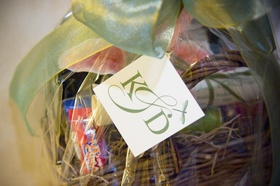 Wicker basket filled with snacks and tied with green ribbon