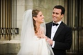 Bride in a veil and groom in a black tuxedo
