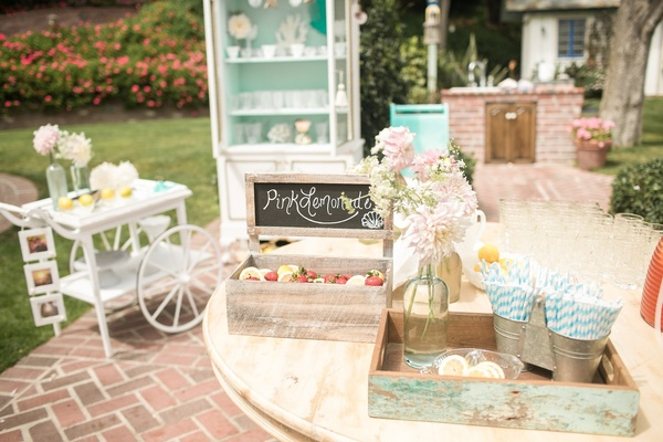Rustic pink lemonade stand with strawberry garnishes