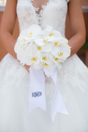 Bride holding small bouquet of all white phalaenopsis orchid flowers and ribbon with monogram