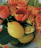 glass bowl filled with orange tulips and roses and lemons