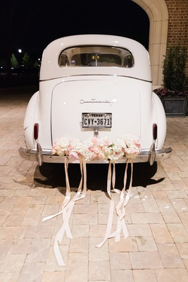 vintage white getaway car with blush flowers and ribbons tied to the back