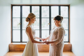 blonde bride with low chignon bun holds hands with mother of the bride in neutral dress